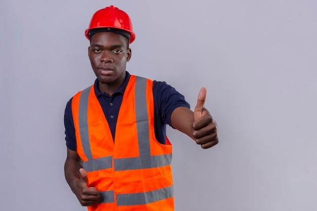 Junger afroamerikanischer baumeistermann, der bauweste und sicherheitshelm trägt, der daumen oben stehend zeigt