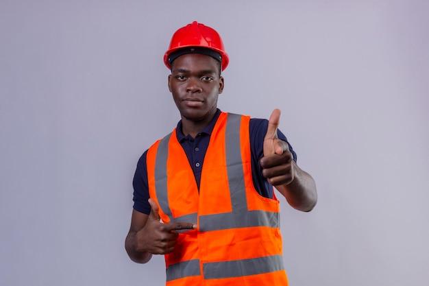 Junger afroamerikanischer baumeistermann, der bauweste und sicherheitshelm trägt, der mit dem finger zeigt, der selbstbewusst steht