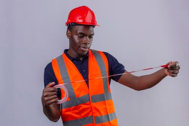 Junger afroamerikanischer baumeistermann, der bauweste und sicherheitshelm trägt, der unter verwendung des maßbandes betrachtet, das es stehend betrachtet