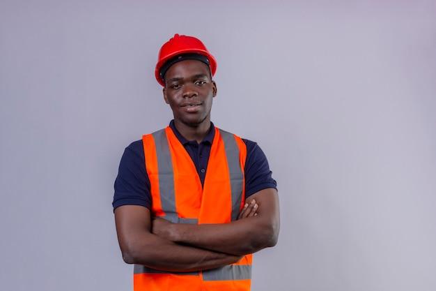Junger afroamerikanischer baumeistermann, der bauweste und sicherheitshelm trägt, die mit den armen gekreuzt mit dem selbstbewussten lächeln auf lokalisiertem weiß stehen