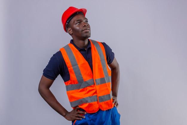 Junger afroamerikanischer baumeistermann, der bauweste und sicherheitshelm trägt, die mit ernstem gesicht stehend aufblicken