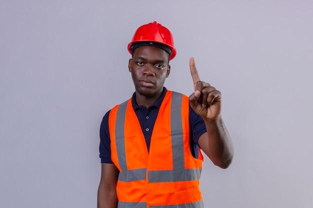 Junger afroamerikanischer baumeistermann, der bauweste und sicherheitshelm trägt, die mit finger oben warnung vor gefahr auf isoliertem weiß stehen