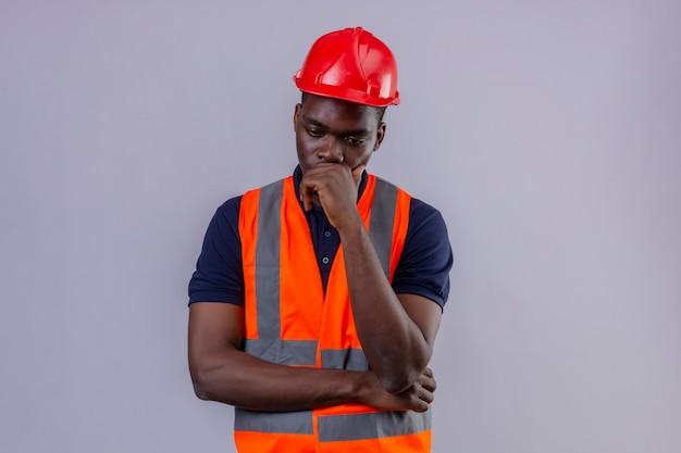 Junger afroamerikanischer baumeistermann, der bauweste und sicherheitshelm trägt, die mit hand auf kinn denken und versuchen, wahl besorgtes stehen zu treffen