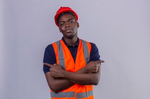 Junger afroamerikanischer baumeistermann, der bauweste und sicherheitshelm trägt, hält gekreuzte hände, die mit fingern mit dem sicheren blick stehend zeigen