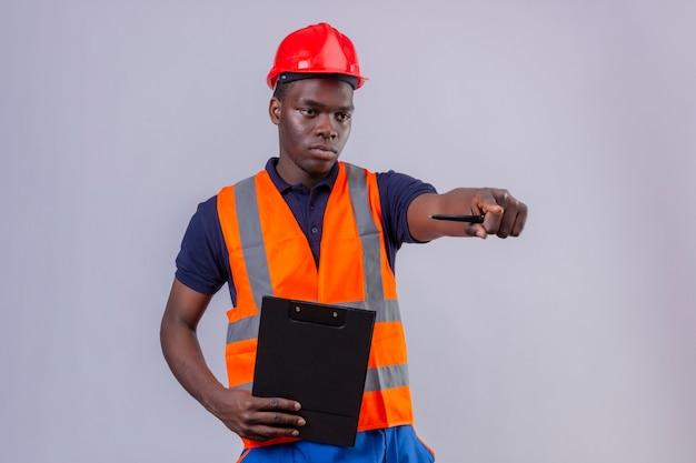 Junger afroamerikanischer baumeistermann, der bauweste und sicherheitshelm trägt zeigefinger in die entfernung mit ernstem ausdruck stehend