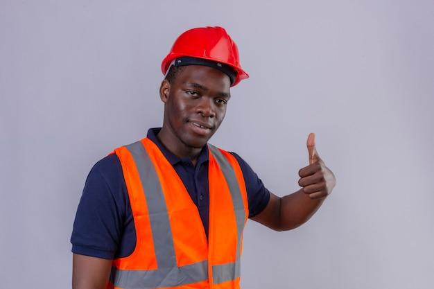 Junger afroamerikanischer baumeistermann, der bauweste und sicherheitshelm trägt, zeigt daumen oben mit lächeln auf gesicht stehend