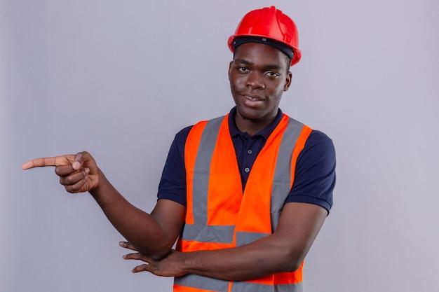 Junger afroamerikanischer baumeistermann, der bauweste und sicherheitshelm trägt, zeigt mit dem finger zur seite, die auf lokalem weiß zuversichtlich schaut