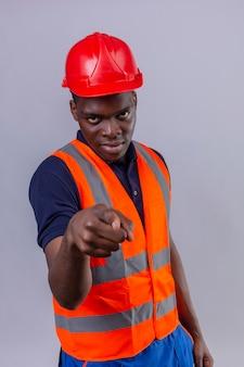 Junger afroamerikanischer baumeistermann, der bauweste und sicherheitshelm trägt, zeigt unzufrieden und frustriert wütend und wütend mit ihnen auf isoliertem weiß