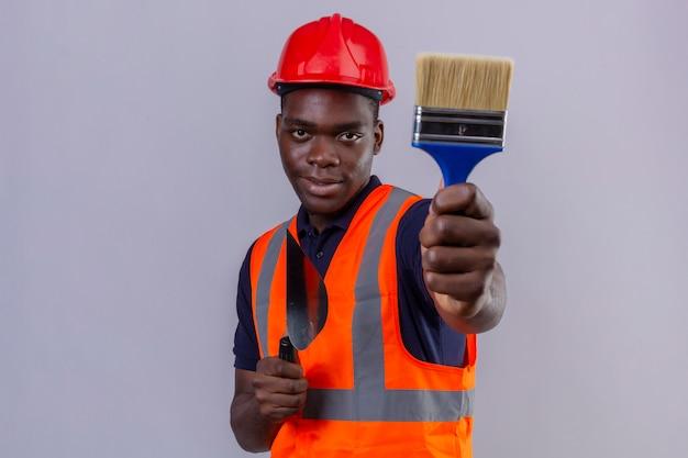 Junger afroamerikanischer baumeistermann, der bauweste und sicherheitshelm zeigt, die pinsel ausdehnen, der sicher auf lokalisiertem weiß schaut