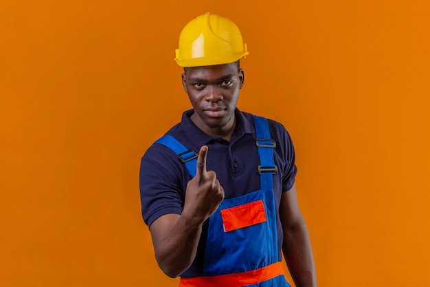 Junger afroamerikanischer baumeistermann, der konstruktionsuniform und sicherheitshelm trägt, der mit zeigefinger zeigt, der nummer eins zeigt, das mit zuversichtlichem ernstem ausdruck steht