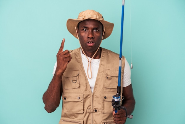 Junger afroamerikanischer fischer, der auf blauem hintergrund isolierte stange hält und eine großartige idee hat, konzept der kreativität.
