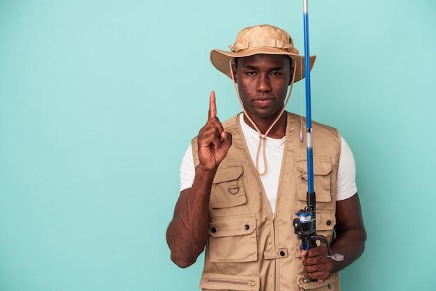 Junger afroamerikanischer fischer, der die stange auf blauem hintergrund isoliert hält und die nummer eins mit dem finger zeigt.