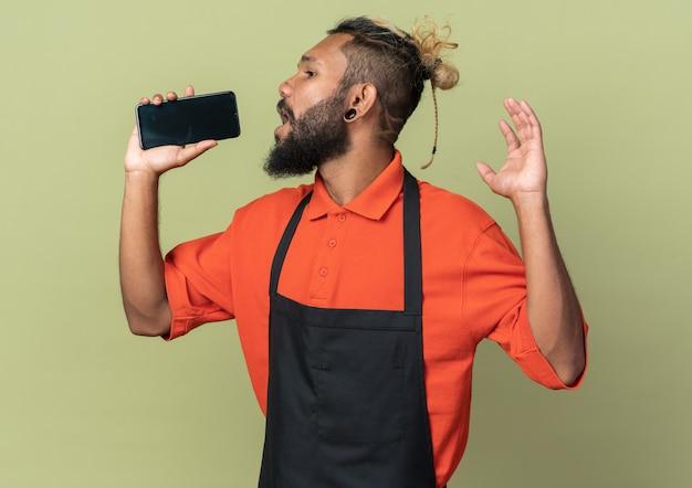 Junger afroamerikanischer friseur in uniform, der auf die seite schaut und die hand in der luft hält und das mobiltelefon als mikrofon singt, isoliert auf olivgrüner wand