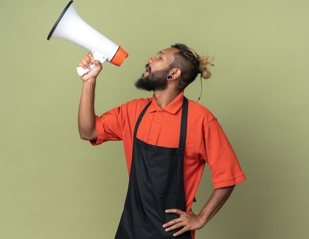 Junger afroamerikanischer friseur in uniform, der die hand auf der taille hält und auf die seite schaut, die vom lautsprecher isoliert auf olivgrüner wand spricht?