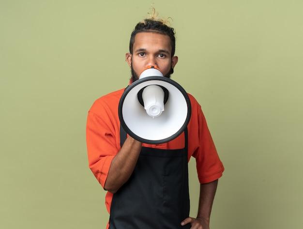 Junger afroamerikanischer friseur in uniform, der vom lautsprecher spricht und die hand auf der taille hält