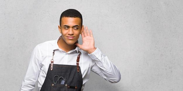 Junger afroamerikanischer friseurmann, der auf etwas hört, indem er hand auf das ohr auf strukturierte wand setzt