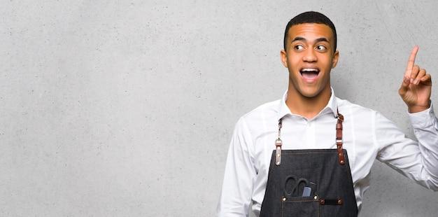 Junger afroamerikanischer friseurmann, der beabsichtigt, die lösung beim anheben eines fingers auf strukturierter wand zu realisieren