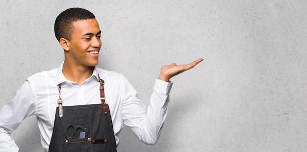 Junger afroamerikanischer friseurmann, der copyspace eingebildet auf der palme hält, um eine anzeige auf strukturierter wand einzufügen