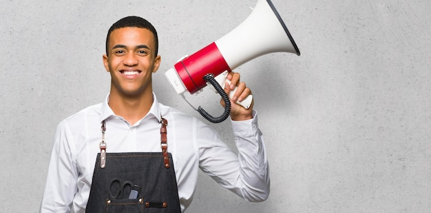 Junger afroamerikanischer friseurmann, der ein megaphon auf strukturierter wand hält