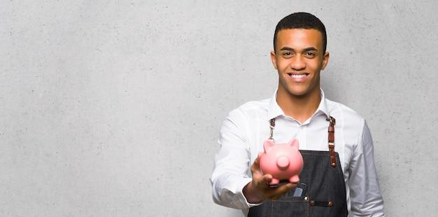 Junger afroamerikanischer friseurmann, der ein sparschwein auf strukturierter wand hält