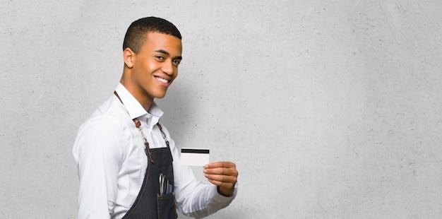 Junger afroamerikanischer friseurmann, der eine kreditkarte hält