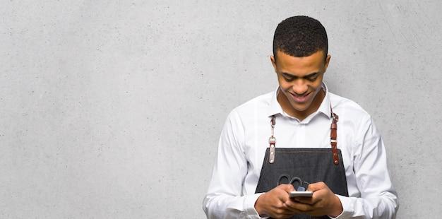 Junger afroamerikanischer friseurmann, der eine mitteilung mit dem mobile auf strukturierter wand sendet