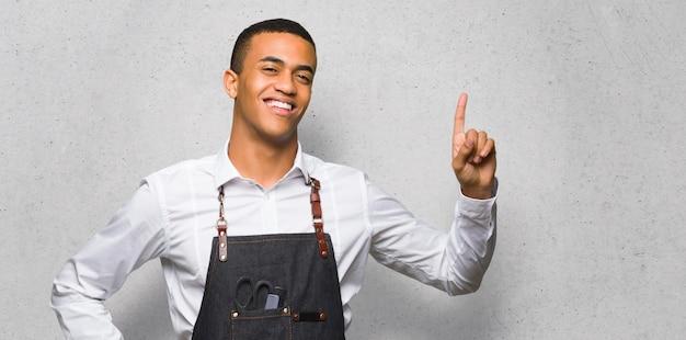 Junger afroamerikanischer friseurmann, der einen finger im zeichen des besten auf strukturierter wand zeigt und anhebt