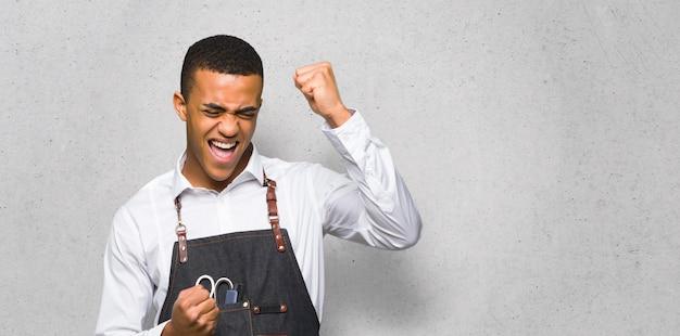 Junger afroamerikanischer friseurmann, der einen sieg auf strukturierter wand feiert