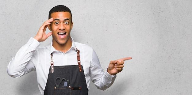 Junger afroamerikanischer friseurmann, der finger auf die seite zeigt und ein produkt auf strukturierter wand darstellt