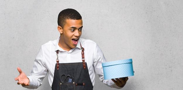 Junger afroamerikanischer friseurmann, der geschenkbox in den händen auf strukturierter wand hält