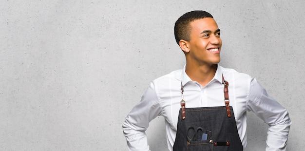 Junger afroamerikanischer friseurmann, der mit den armen an der hüfte aufwirft und auf strukturierter wand lacht