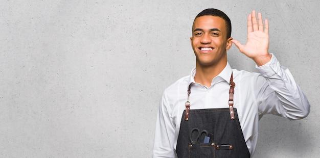 Junger afroamerikanischer friseurmann, der mit der hand mit glücklichem ausdruck auf strukturierter wand begrüßt