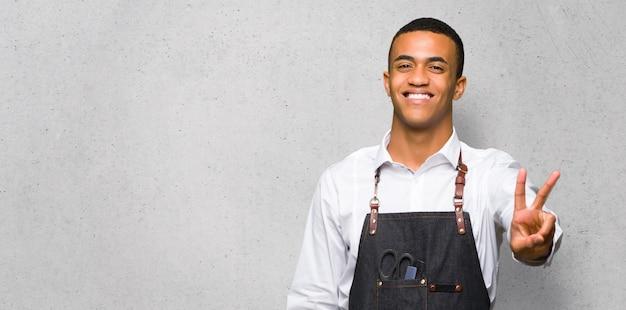Junger afroamerikanischer friseurmann, der siegeszeichen auf strukturierter wand lächelt und zeigt