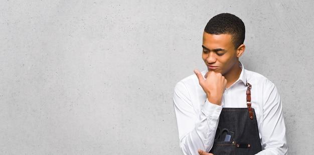 Junger afroamerikanischer friseurmann, der unten mit der hand auf dem kinn auf strukturierter wand schaut