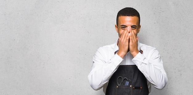Junger afroamerikanischer friseurmann, der viel bei der abdeckung des munds auf strukturierter wand lächelt
