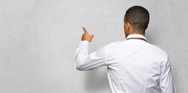 Junger afroamerikanischer friseurmann, der zurück mit dem zeigefinger auf wand zeigt