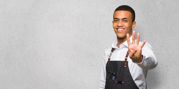 Junger afroamerikanischer friseurmann glücklich und vier mit den fingern auf strukturierter wand zählend