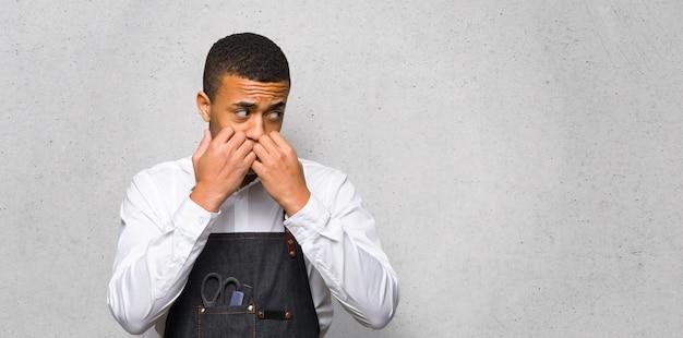 Junger afroamerikanischer friseurmann ist ein bisschen nervös und erschrocken, hände zum mund auf strukturierte wand zu setzen