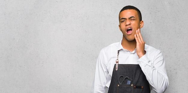 Junger afroamerikanischer friseurmann mit zahnschmerzen auf strukturierter wand