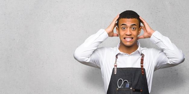 Junger afroamerikanischer friseurmann nimmt hände auf kopf, weil migräne auf strukturierter wand hat