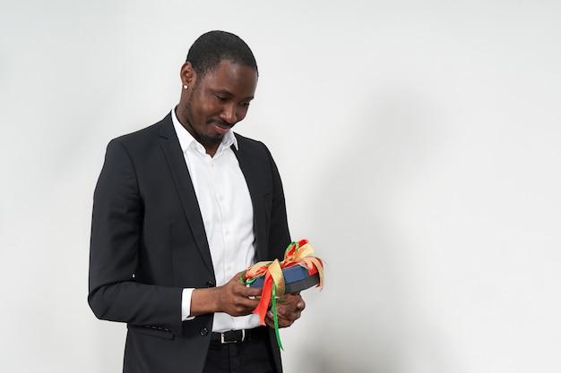 Junger afroamerikanischer geschäftsmann, der anzug hält geschenk hält. gegenwärtiges konzept