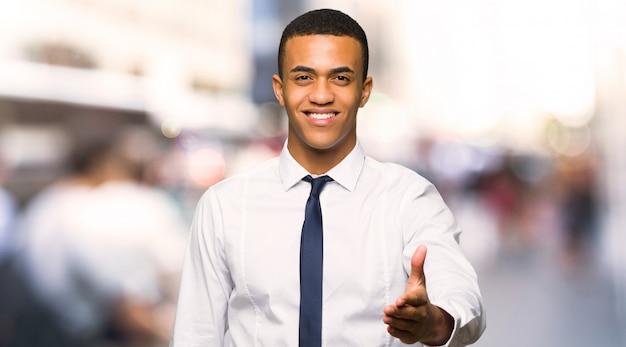 Junger afroamerikanischer geschäftsmann, der hände für das schließen eines guten deals in der stadt rüttelt