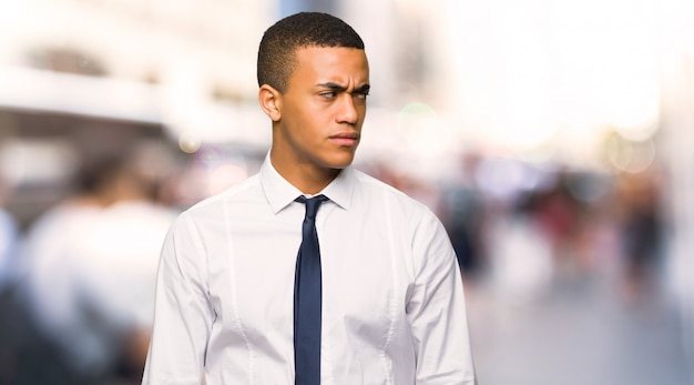 Junger afroamerikanischer geschäftsmann, der in der stadt gestört glaubt