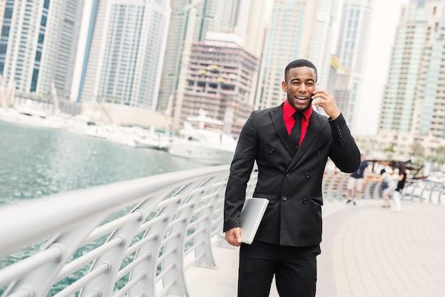 Junger afroamerikanischer geschäftsmann, der in dubai marine steht und auf seinem handy mit lächeln auf seinem gesicht spricht.