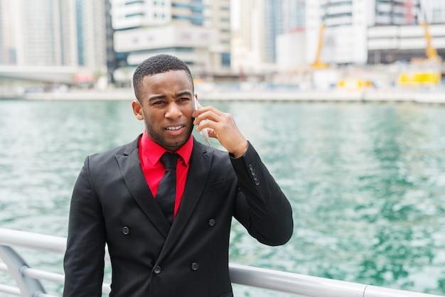 Junger afroamerikanischer geschäftsmann, der in dubai marine steht und mit besorgtem gesichtsausdruck auf seinem handy spricht.