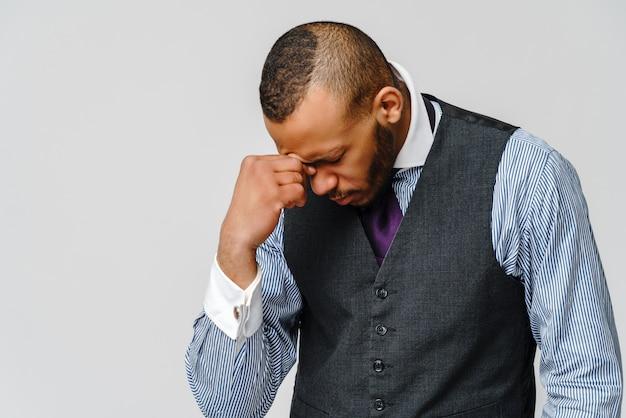 Junger afroamerikanischer geschäftsmann, der kopf wegen der kopfschmerzen und des stresses berührt.