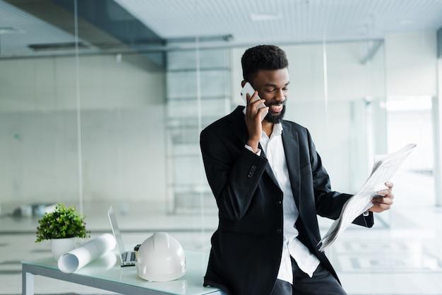 Junger afroamerikanischer geschäftsmann, der zeitung liest und am telefon in seinem büro spricht