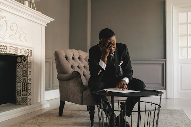Junger afroamerikanischer geschäftsmann im anzug, der notizen von hochwertigem foto macht