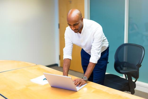 Junger afroamerikanischer geschäftsmann im büro mit seinem laptop