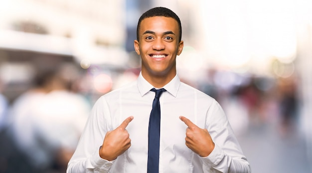 Junger afroamerikanischer geschäftsmann mit überraschungsgesichtsausdruck in der stadt